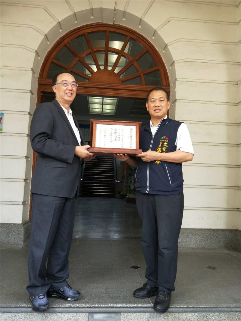 由文資局施國隆局長(左)致贈台中州廳國定古蹟指定證書,由文化局張大春局長(右)代表授贈。